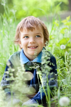 Portrait of small boy sitting on grass in park photo
