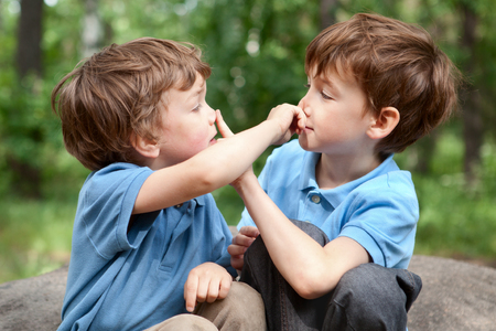 Two brothers click on  nose, outdoor 免版税图像