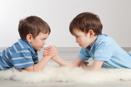 Arm wrestling and two brothers, indoor