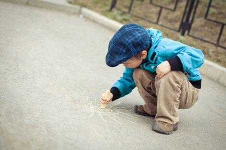 Boy drawing on road. Outdoor. photo