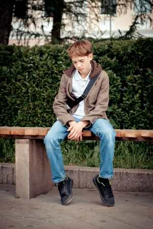 Sad teen sitting on bench in park photo