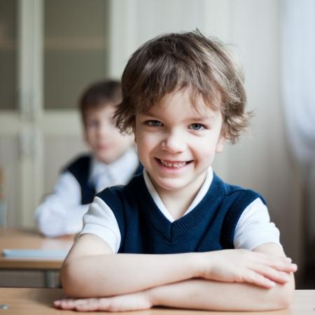 diligente: Diligente preescolar sentado en el escritorio, el aula