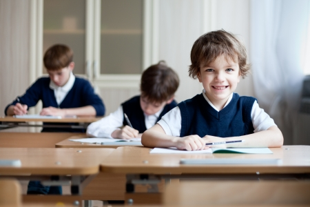 school exam: Diligent preschool sitting at desk, classroom