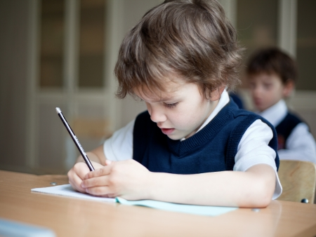 diligent: Diligent preschool sitting at desk, classroom