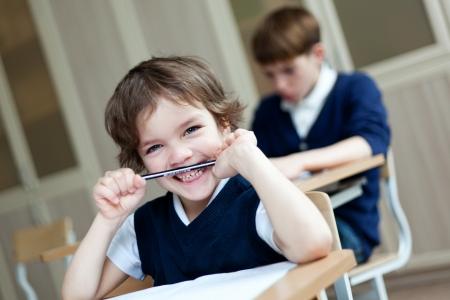 Diligent preschool sitting at desk, classroom