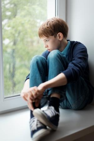 Sadsad tiener zittend op venster