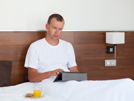 Portrait of man using tablet computer in bedroom photo