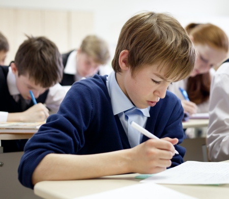 thoughtful school boy struggling to finish test in class.