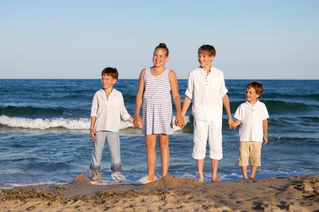 HAppy children are standing on beach, outdoor photo