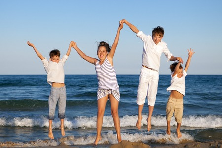 HAppy children are jumping on beach, outdoor photo