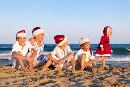 HAppy Children in santa claus hat  are sitting on beach, outdoor Standard-Bild