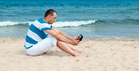 Portrait of man using tablet computer in  coastline, photo