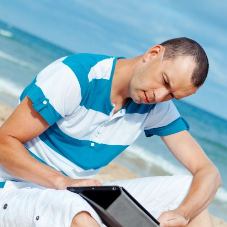 Portrait of man using tablet computer in  coastline, photo