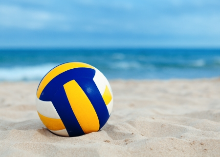 ball is lying on sand near ocean