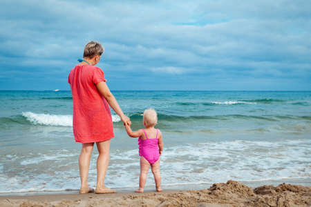 mother and his adorable little daughter at beach photo