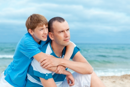father and sons walking on beach, outdoor photo
