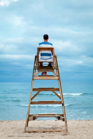 Man sitting on lifeguard chair, outdoor Standard-Bild