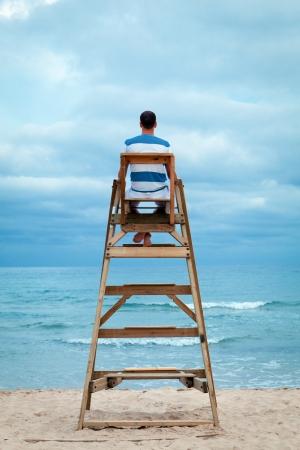 Man sitting on lifeguard chair, outdoor Standard-Bild