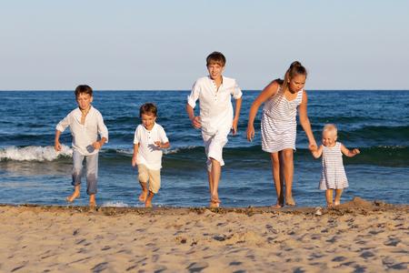 HAppy children are running on beach, outdoor photo