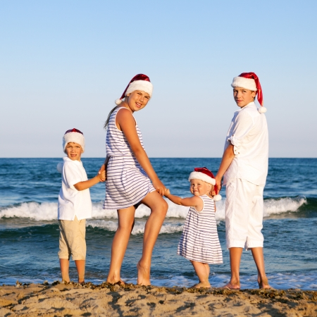 HAppy Children in santa claus hat  are standing on beach, outdoor photo
