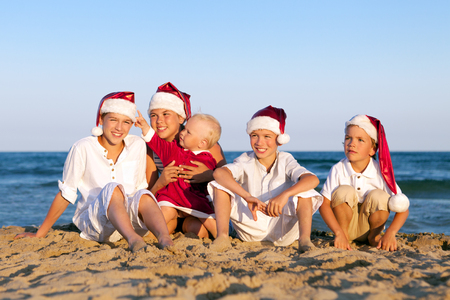 HAppy Children in santa claus hat  are sitting on beach, outdoor photo