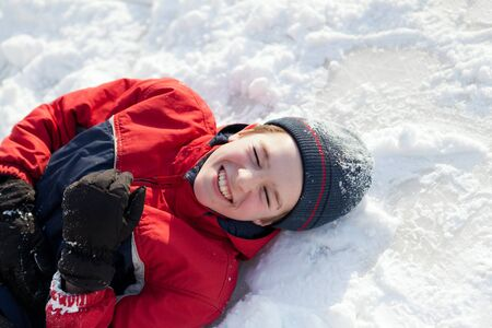 winterwear: Happy boy in winterwear laughing while playing in snowdrift outside