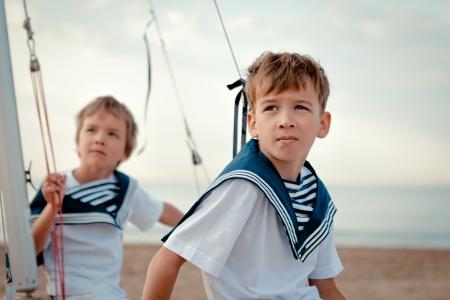 Retrato de jóvenes marineros cerca de yate, al aire libre