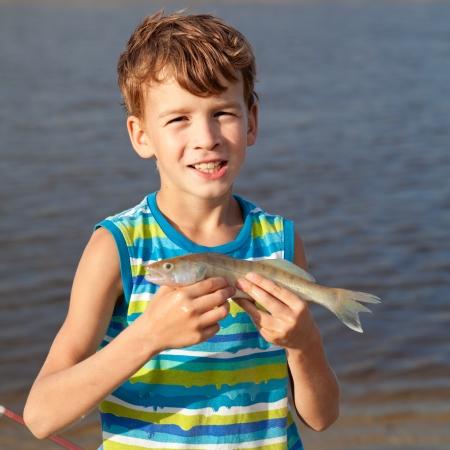 Junge hält Fisch und lächelnd
