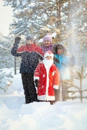 Portrait of happy children and Santa in winter forest photo