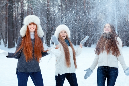 Portrait of three  happy beautiful girls in winter park photo