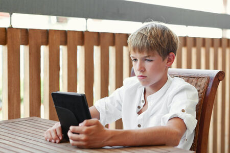 Serious teenager reading e-book, indoor