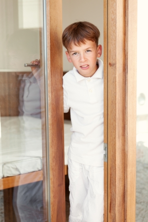 Surprised boy peeks from behind door, indoor photo