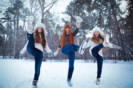 Portrait of three happy nice girls in winter park photo