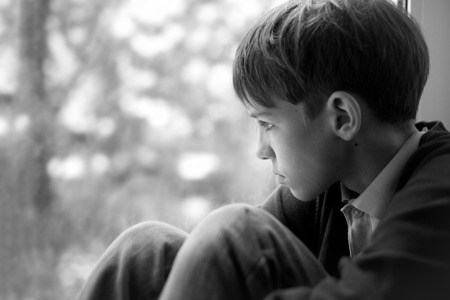 boy sitting: Sad teenager sitting on window, black-and-white photo