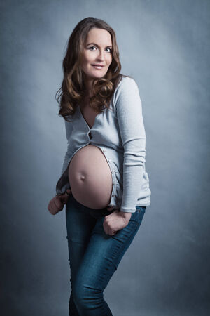 Portrait of beautiful happy pregnant woman in studio, motherhood, monochrome, tummy photo