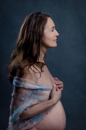 Portrait of beautiful happy pregnant woman in studio, motherhood, monochrome, tummy photo