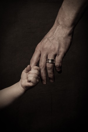 Child's small hand holding finger of his father, dark key