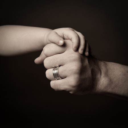 Adult male hand holding hand of baby, dark key