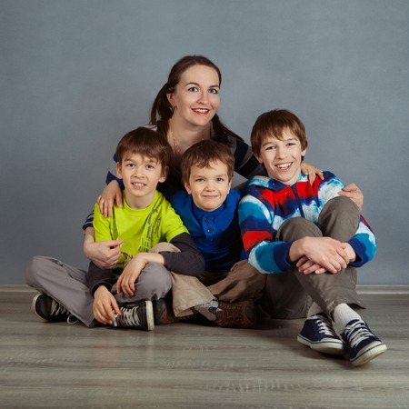 Portrait of happy mother and three sons on gray background