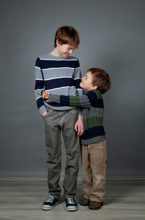 Portrait von zwei Brüdern auf grauem Hintergrund