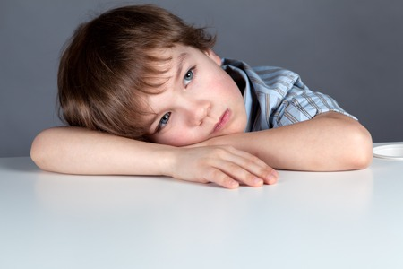 Thinking  schoolchild sitting at desk, studio, training