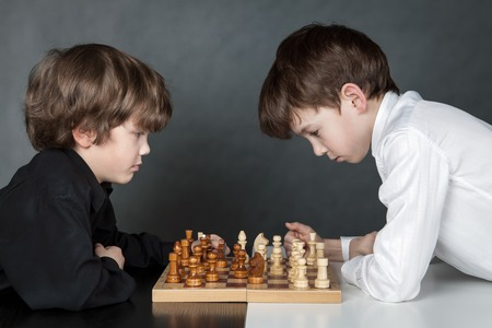 Two serTwo serious boy playing chess.