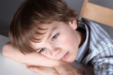 Thinking  schoolchild sitting at desk