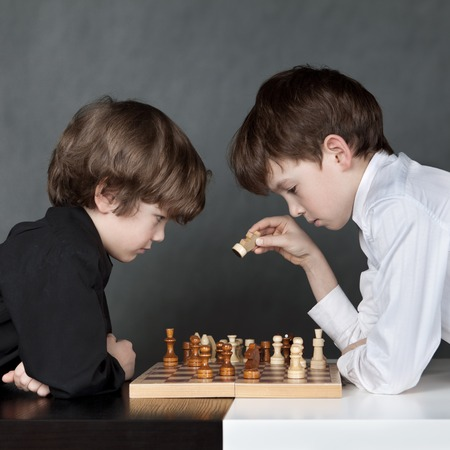 Two serTwo serious boy playing chess, studio