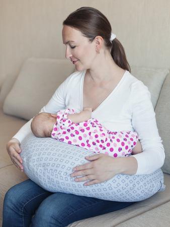 Happy mother breast feeding her newborn in room, indoor