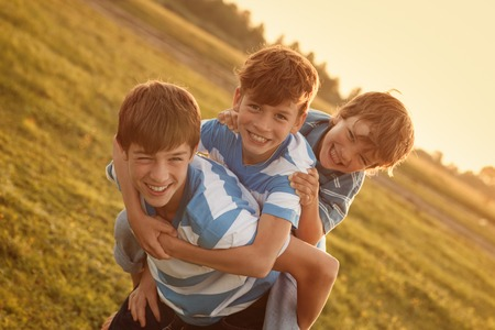 Portrait of three happy cheerful brothers at sunset, outdoor photo