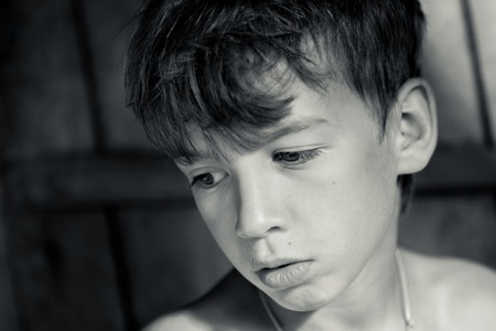 Portrait of sad, pensive, serious boy, black and white photo Standard-Bild