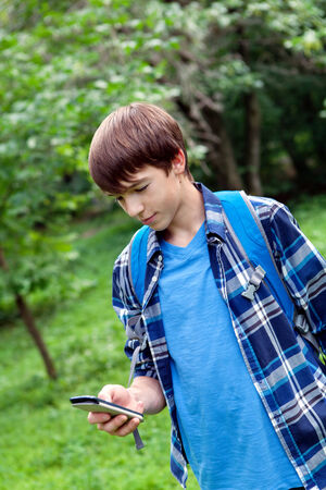 children at play: Young handsome happy modern teen talking on phone in summer park, outdoor, schoolboy