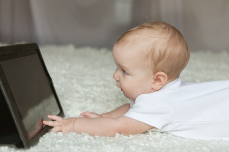 Baby girl playing with tablet, indoor