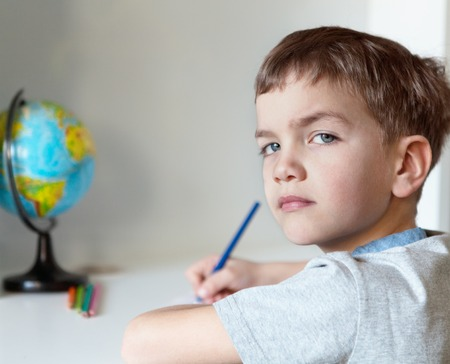 Serious pensive pupil sits at desk, writing in notebook, class, indoor